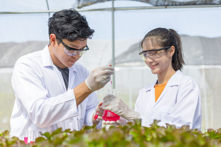 Smiling scientists performing experiment in greenhouse