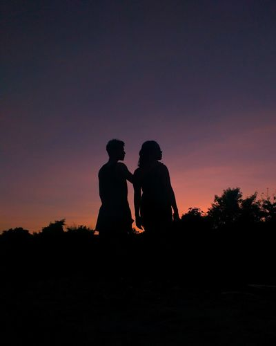 Silhouette men standing against orange sky
