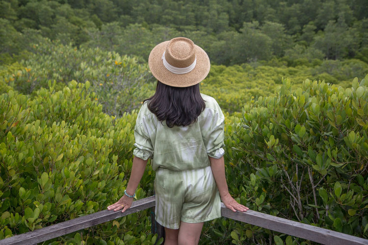 Rear view of woman standing by railing against forest