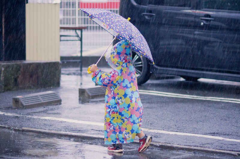 Woman with umbrella on road in city