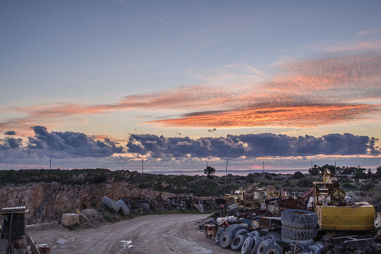 Empty Road By Abandoned Bulldozer And Tires At Junkyard During Sunset
