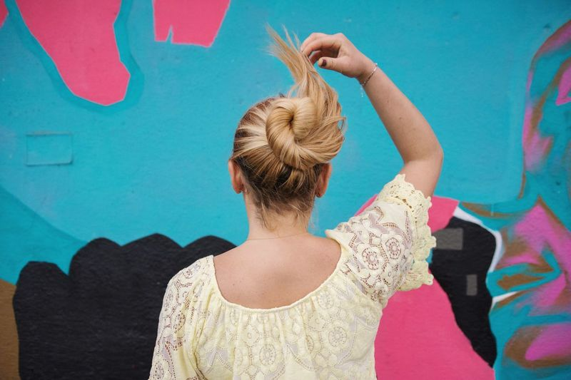 Rear view of woman with hair bun standing against wall