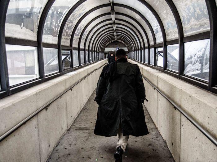 Rear View Of Man In Jacket Walking On Elevated Walkway