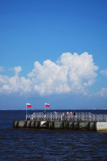 Russian flags on pier over sea against sky