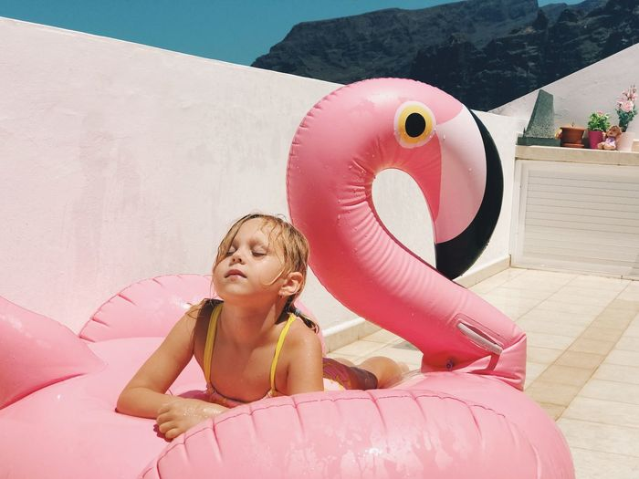Girl Relaxing On Inflatable Ring In Swan Shape During Sunny Day
