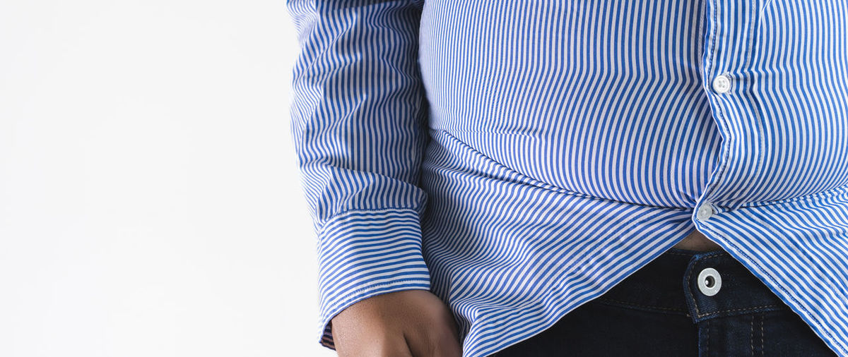 Midsection of man wearing striped shirt while standing against white background