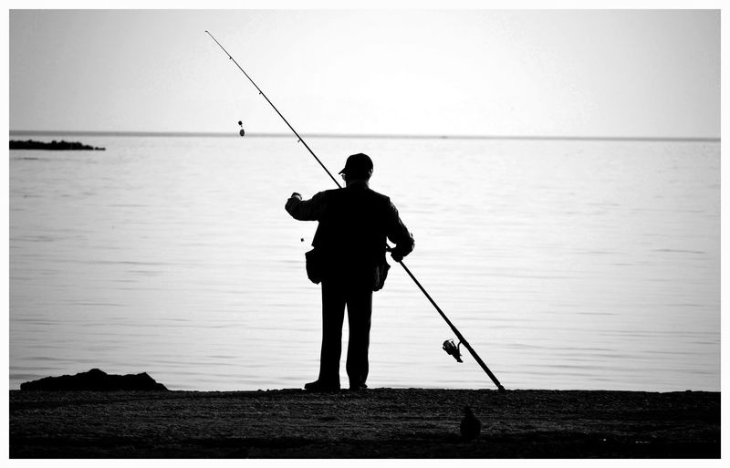Rear View Of Silhouette Man Fishing In Sea