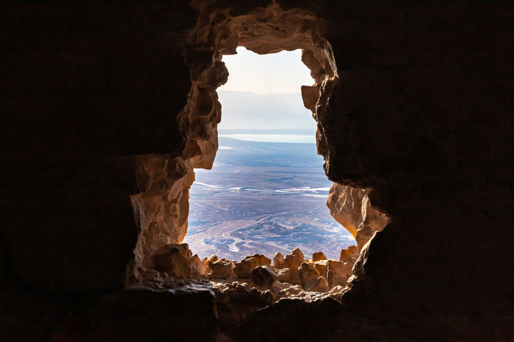 Scenic view of landscape seen through cave