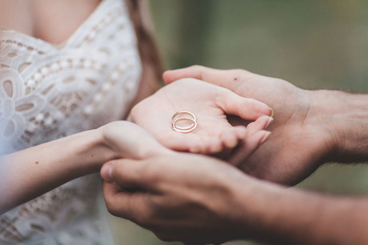 Midsection of young couple holding engagement rings