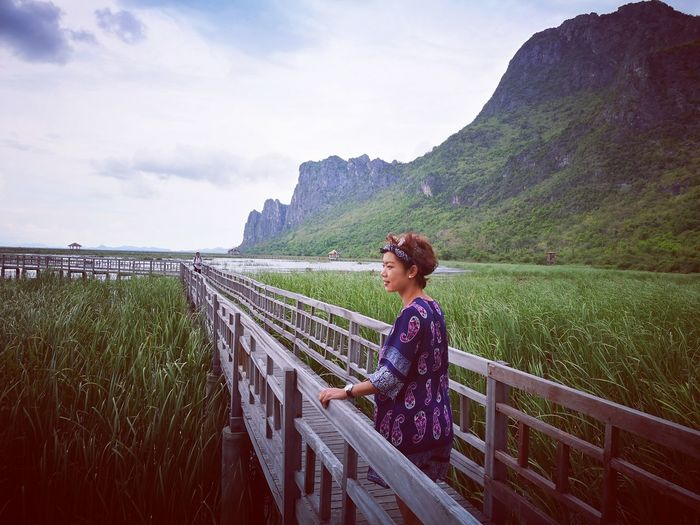 Thoughtful woman standing on wooden footbridge over grassy field against sky