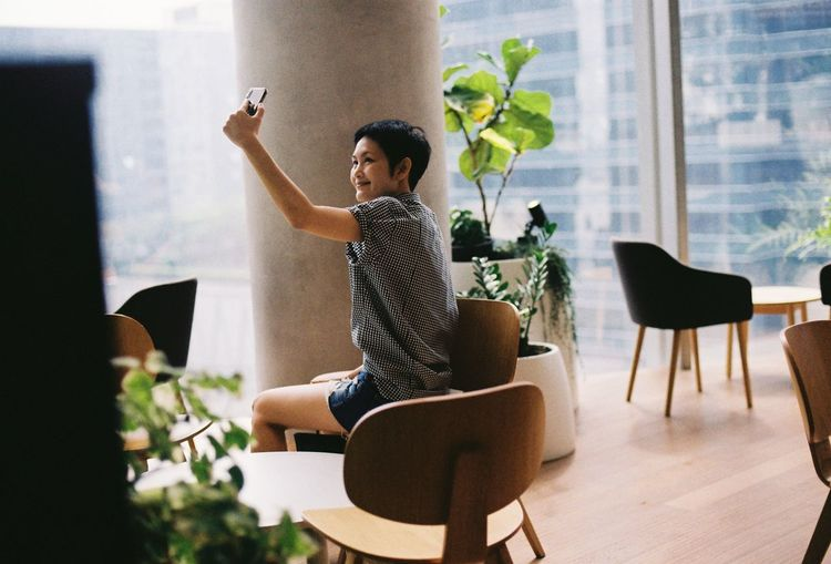 Woman taking selfie through mobile phone against window
