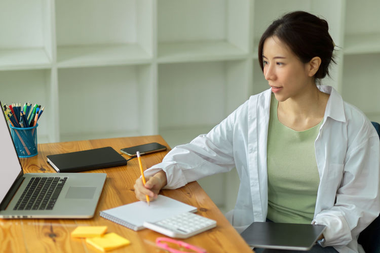 Mid adult woman using smart phone while sitting on table