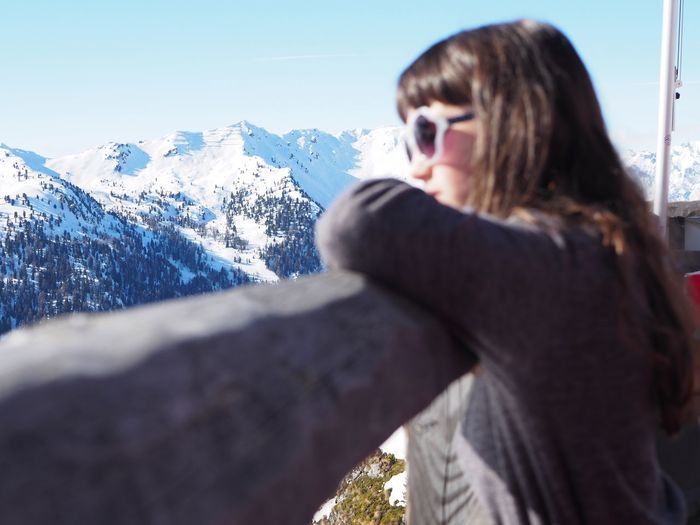 Side view of girl against snowcapped mountains