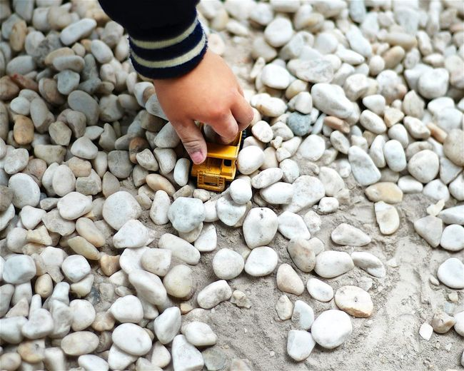 Cropped image of kid playing with toy car