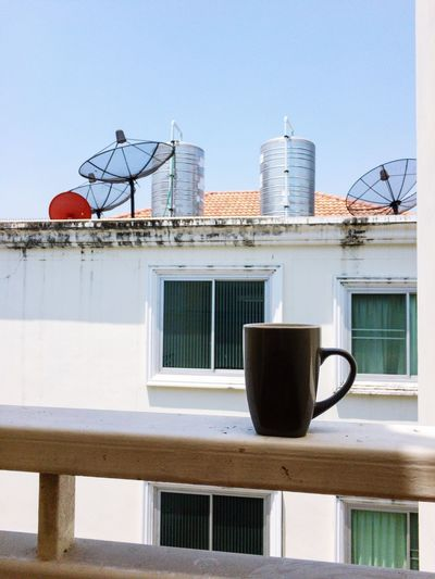 Coffee cup on railing against building