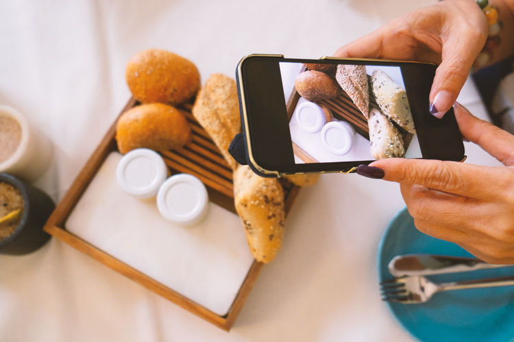 Dinning Bread And Jam Breakfast Communication Connection Finger Food Food And Drink Hand Holding Human Body Part Human Hand Indoors  Meal Mobile Phone One Person Photography Themes Portable Information Device Real People Screen Shooting Smart Phone Table Technology Wireless Technology
