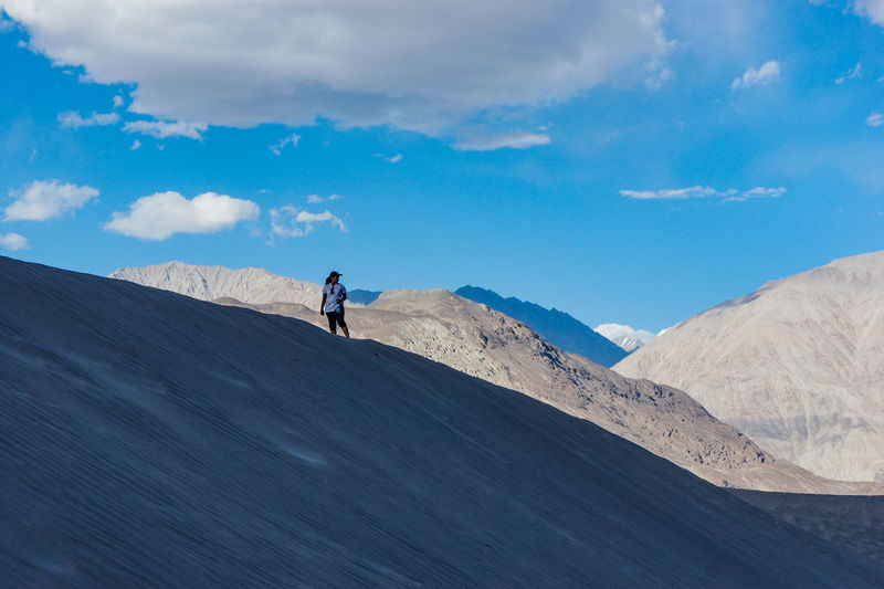 Young women on sand dune at high altitude in nubra valley against sky