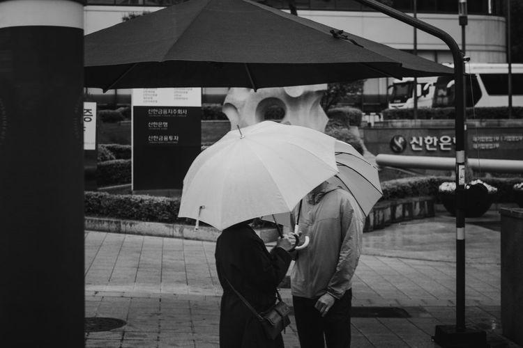 Rear view of people walking on street during rainy season