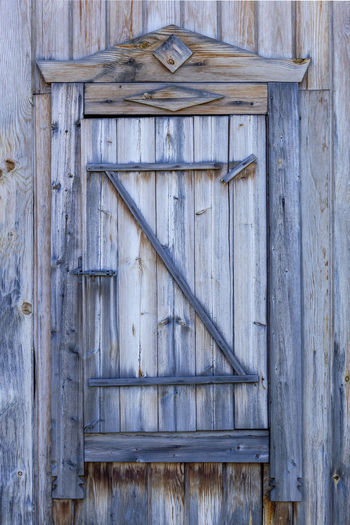 Spare wooden door in an old wooden house. front view.