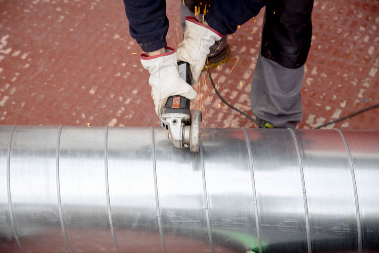 High angle view of industry worker cutting steel with angle grinder