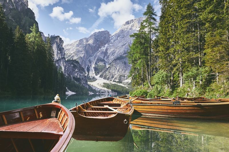 Wooden boats on lake. Beautiful sunny morning at Lago di Braies in Dolomite Alps - South Tyrol, Italy Calm Dolomites Sunlight Travel Adventure Beauty In Nature Braies Lake Day Idyllic Italy Lago Di Braies Lake Landscape Mountain Mountain Range Nature No People Outdoors Rowboat Scenics - Nature Tranquil Scene Tranquility Travel Destinations Tree Water