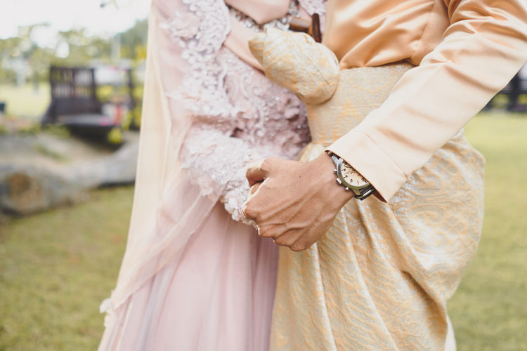 Midsection of bride and bridegroom standing outdoors