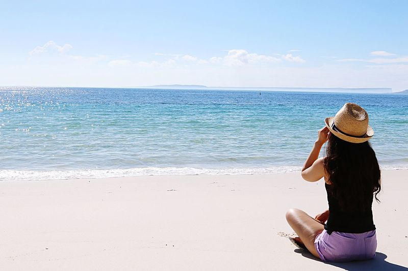The beautiful girl is wearing hat sitting on the beach in sunny day background. Sea Beach Water Land Sky Real People One Person Outdoors Scenics - Nature Lifestyles Nature Horizon Over Water Horizon Rear View Beauty In Nature Day Women Child Leisure Activity Creative Space