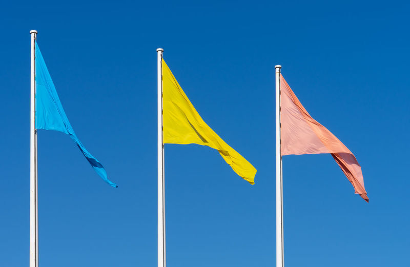 #urbanana: The Urban Playground Blue Flag Summer In The City Blue Blue Sky Clear Sky Day Environment Flag Flags Flags In The Wind  Low Angle View Multi Colored Nature No People Outdoors Patriotism Pole Red Red Flag Shape Sky Sunlight Waving Wind Yellow Yellow Flag