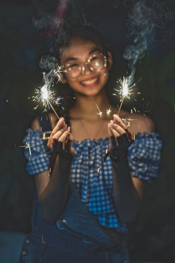 Portrait of young woman holding sparklers at night