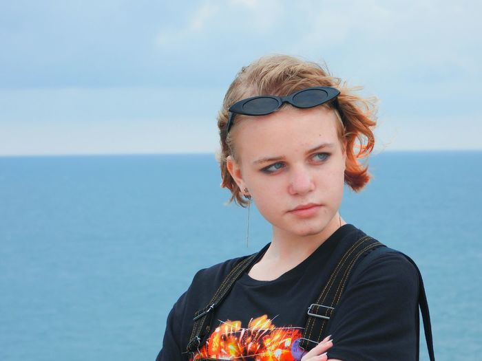 Portrait of young woman against sea against sky