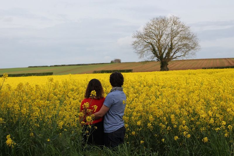 Rear view of couple standing amidst plants against cloudy sky