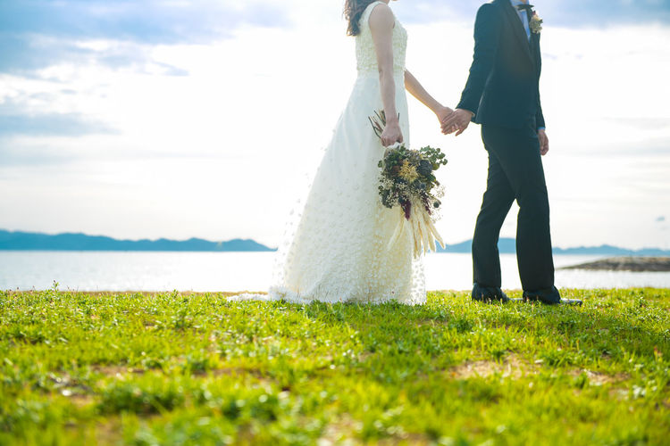Low section of bride and bridegroom holding hands by lake on land