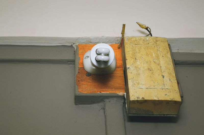 Low angle view of light bulb with door bell on gray wall
