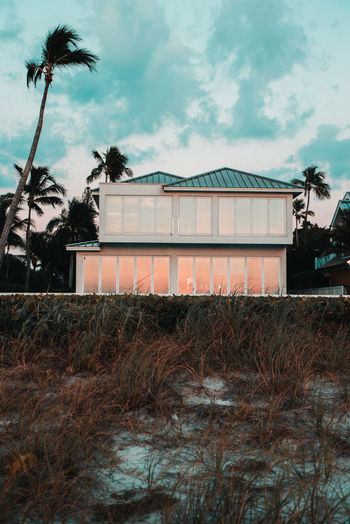 House by palm trees against sky
