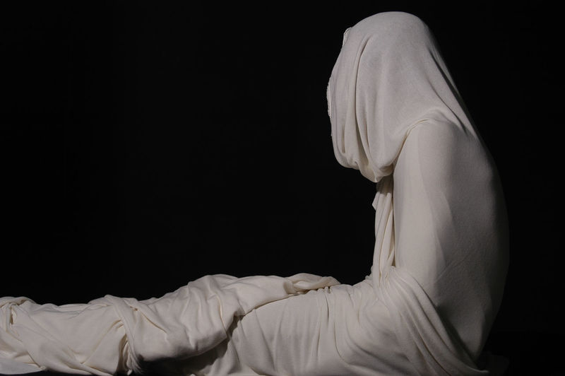Person wrapped in white fabric against black background