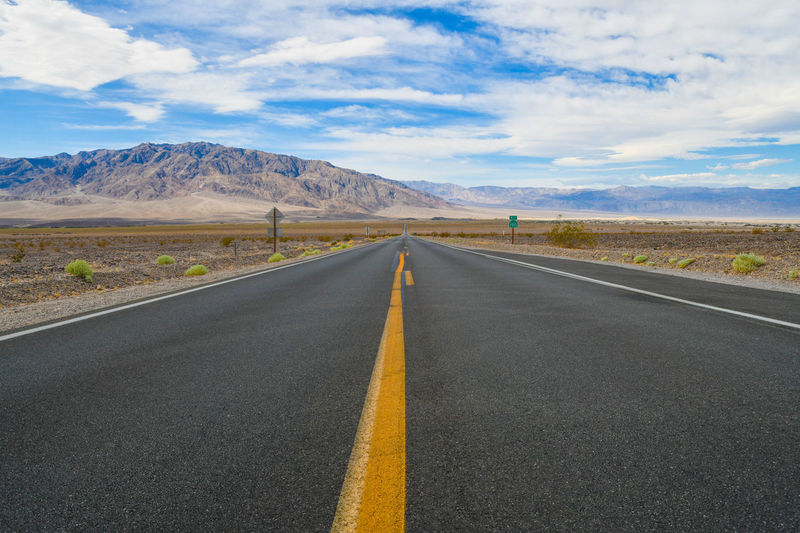 Scenic view of empty road by mountains against sky