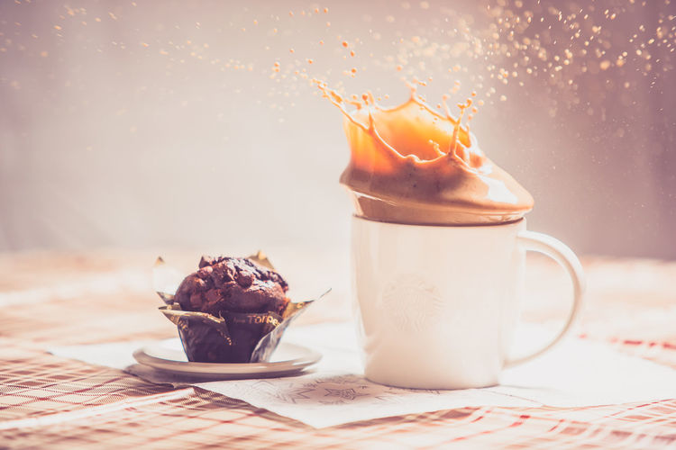 Coffee splashing in cup by muffin on table