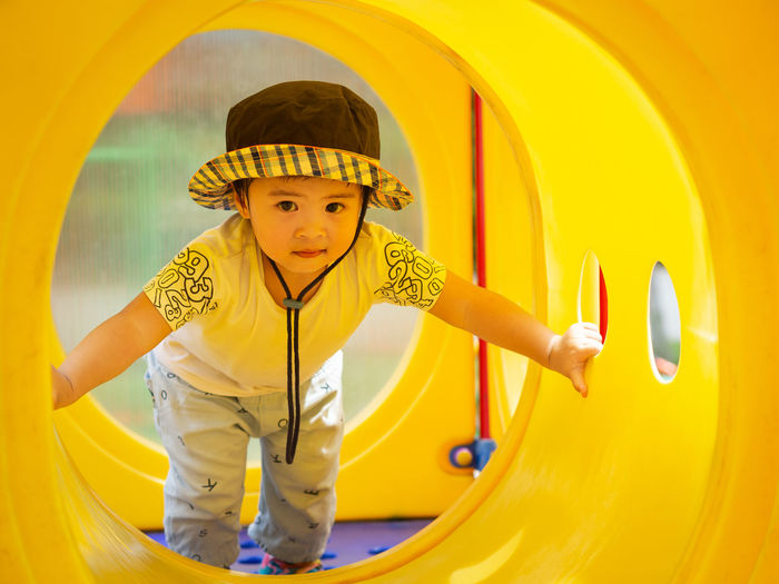 Happy little girl playing at the playground. Children, Happy, Family Concept. Yellow Childhood One Person Child Real People Looking At Camera Front View Portrait Leisure Activity Lifestyles Boys Males  Men Cute Outdoor Play Equipment Playground Indoors  Innocence