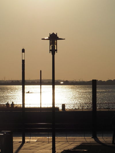 Silhouette street light by sea against clear sky during sunset