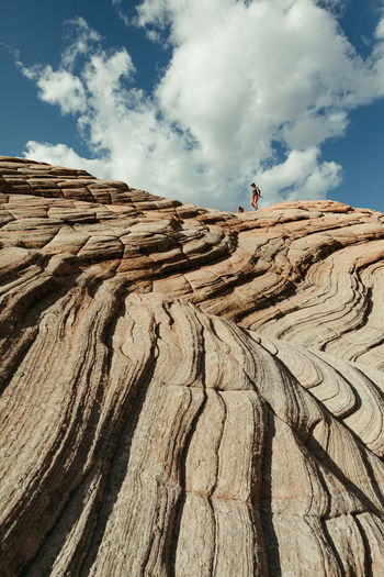 Low angle view of people on rock against sky