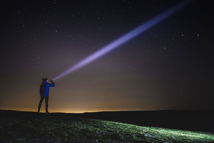 Man pointing flashlight on star field while standing on mountain