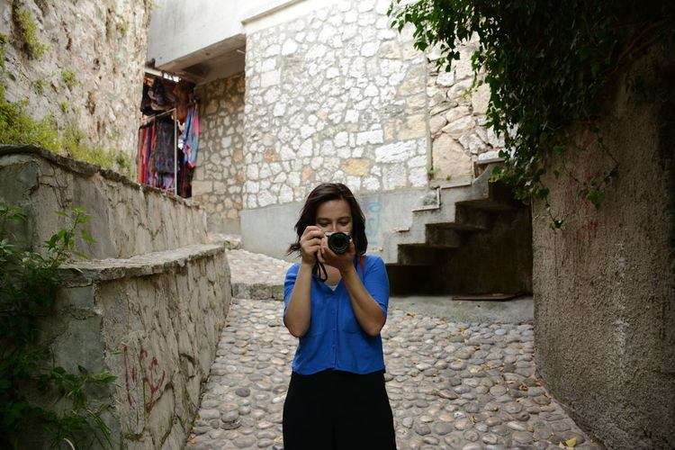 Young woman photographing while standing at alley