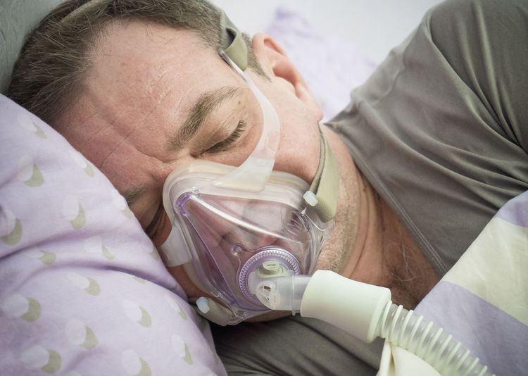 Close-up of patient wearing oxygen mask while lying on bed in hospital