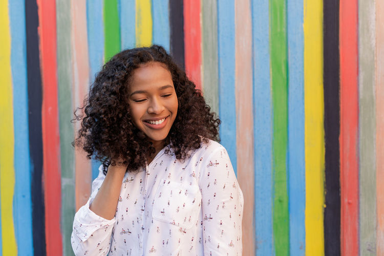 Close-Up Of Young Woman Smiling Against Colorful Wall