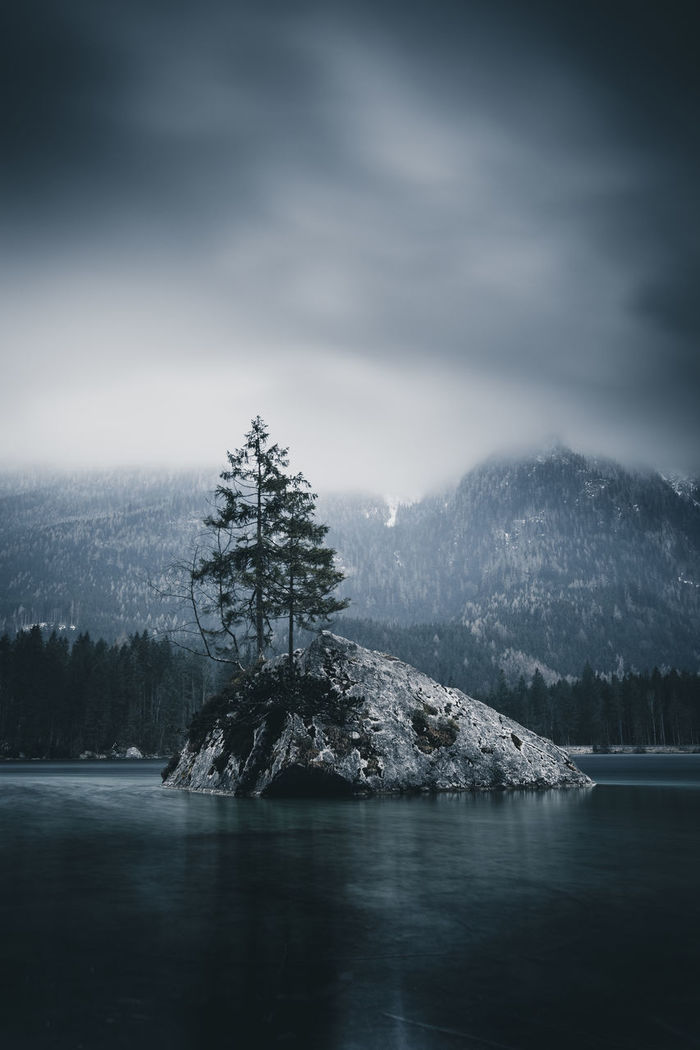 Scenic view of lake and mountains during foggy weather