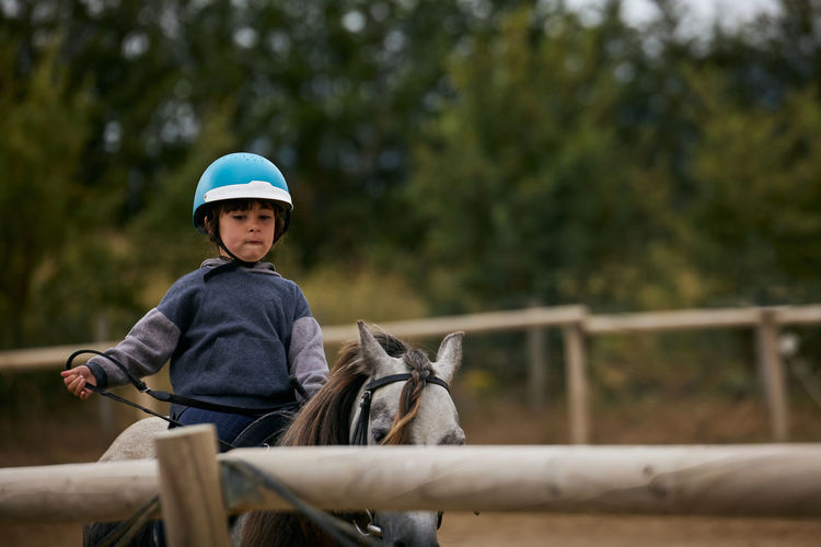 5-year-old girl riding on a horse, in a hipico club. infalltil sport concept