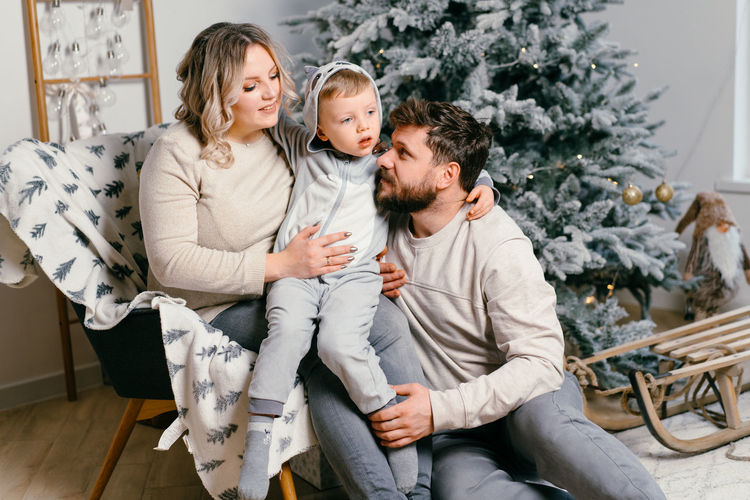 Full length of father and woman sitting on christmas tree