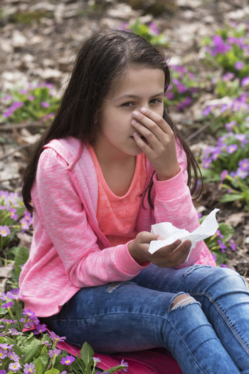 Young girl in a forest with allergy Medicine Sitting Allergic Allergy Blooming Blowing Caucasian Eyes Flowers Forest Girl Health Ill Infection Long Hair Napkin Nose One Pollen Season  Sensitive Sick Sneezing Teenager Treatment