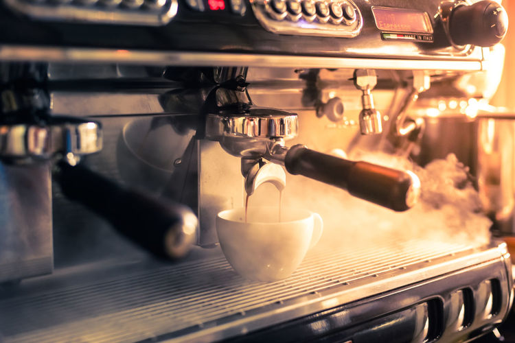 Close-up of machinery pouring coffee in cup at cafe