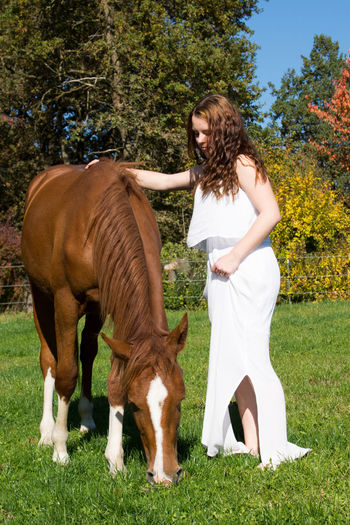 Side view of young woman with horse standing on grassy field against trees